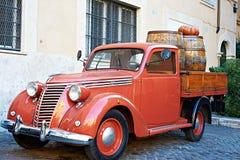 Uitstekende rode bestelwagen met oude houten vaten wijn Stock Foto's