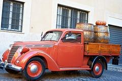 Uitstekende rode bestelwagen met oude houten vaten wijn Stock Foto