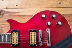 Uitstekende rode gitaar op oude houten oppervlakte Stock Afbeeldingen