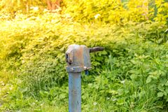 Uitstekende roestige de handpomp van de waterfontein in Russisch dorp Verlaten waterbron royalty-vrije stock afbeeldingen