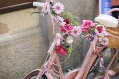 Uitstekende Roze fiets met mand van bloemen Royalty-vrije Stock Afbeeldingen