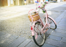 Uitstekende Roze fiets met mand van bloemen Stock Foto