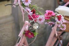 Uitstekende Roze fiets met mand van bloemen Stock Fotografie