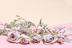 Uitstekende rozen en witte bloemen op de roze achtergrond stock fotografie