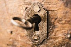 Uitstekende sleutel in slot van houten borst stock afbeeldingen
