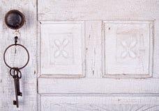 Uitstekende sleutels die op een uitstekende deur hangen Stock Fotografie