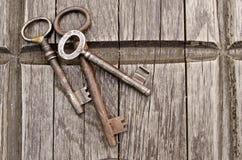 Uitstekende sleutels op oude houten achtergrond Close-up Drie oude, rustieke sleutels op de lijst Stock Foto