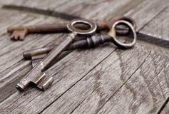 Uitstekende sleutels op oude houten achtergrond Close-up Drie oude, rustieke sleutels op de lijst Stock Afbeelding