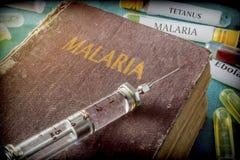 Uitstekende Spuit op een boek van malaria royalty-vrije stock foto's