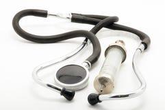 Uitstekende stethoscoop en spuit op witte achtergrond Stock Afbeelding