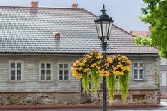 Uitstekende straatlantaarn met het hangen van bloempotten op regenachtige dag Stock Afbeeldingen