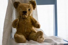 Uitstekende teddy met witte deken op blauwe stoel Stock Fotografie