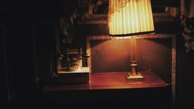 Uitstekende telefoon en retro bureaulamp op lijst stock footage