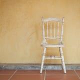Uitstekende toon van witte Uitstekende stoel dichtbij gele oude muur stock foto's