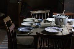 Uitstekende vastgestelde lijst met oude platen en houten stoelen in een slecht binnenland stock afbeeldingen