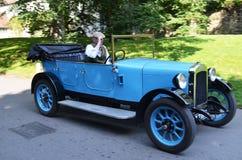 Uitstekende veteraan blauwe auto met bestuurder in de aanpassing van oud kostuum Stock Foto