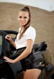 Uitstekende vrouw met cabrioauto Stock Afbeeldingen