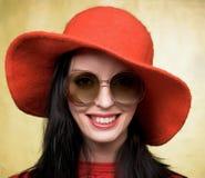 Uitstekende vrouw in zonnebril en rode hoed stock foto's