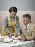 Uitstekende vrouwen dienende lunch aan haar echtgenoot stock foto's
