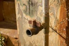 Uitstekende Vuile Plastic Watertapkraan met pvc-Klep - Oude Concrete Textuur - Sunny Warm Day in Huistuin royalty-vrije stock foto's