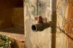 Uitstekende Vuile Plastic Watertapkraan met pvc-Klep - Oude Concrete Textuur - Zonnige Warme Dag in Huistuin stock afbeeldingen