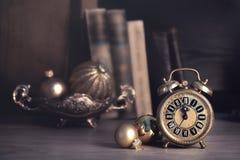 Uitstekende wekker die vijf tot twaalf onder oude boeken tonen Stock Afbeeldingen