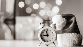 Uitstekende wekker in Santa Claus-hoed met Kerstmisgift stock fotografie