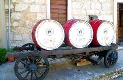 Uitstekende wijnvatten op een oude paardwagen voor een oud steenhuis Stock Foto's