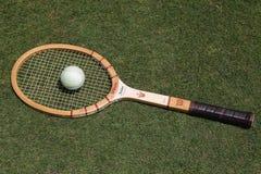 Uitstekende Wilson Jack Kramer-tennisracket en antieke witte tennisbal op de grastennisbaan Royalty-vrije Stock Foto's