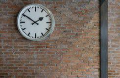 Uitstekende witte muurklok om vorm op de oude bakstenen muurachtergrond Royalty-vrije Stock Afbeelding