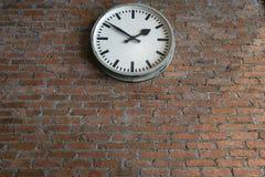Uitstekende witte muurklok om vorm op de oude bakstenen muurachtergrond Royalty-vrije Stock Foto