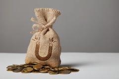 Uitstekende zak met geld op gouden muntstukken Symbool van magneet en het aantrekken van geld stock fotografie