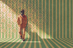 Uitstekende zakenman met gasmasker die zich tegen de muur met retro patroon bevinden royalty-vrije illustratie