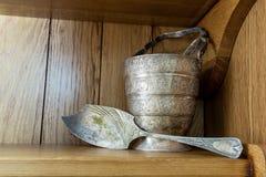 Uitstekende zilveren peddel en ijsemmer met tang op een plank Stock Afbeeldingen