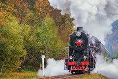 Uitstekende zwarte stoom voortbewegingstrein met wagens op spoorweg royalty-vrije stock fotografie