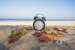 Uitstekende zwarte wekker op de herfstbladeren De abstracte foto van de tijdverandering stock afbeelding