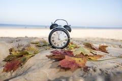 Uitstekende zwarte wekker op de herfstbladeren De abstracte foto van de tijdverandering royalty-vrije stock afbeeldingen