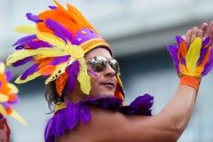 Uitvoerder in gekleurde veren bij Vrolijke trotsparade in Sitges Stock Foto
