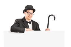 Uitvoerder in kostuum, retro hoed en riet die behing een paneel stellen Stock Fotografie