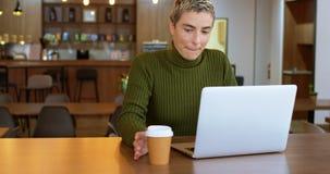 Uitvoerend hebbend koffie terwijl het gebruiken van laptop in bureaucafetaria 4k stock video