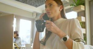 Uitvoerend hebbend koffie terwijl het spreken op mobiele telefoon 4k stock footage