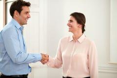 Uitvoerend paar die en handen geven die begroeten glimlachen stock afbeeldingen