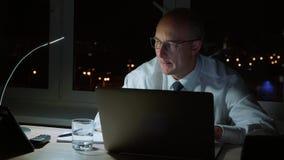 Uitvoerend professioneel manager drinkwater en werkend aan laptop en tablet laat in de avond stock footage