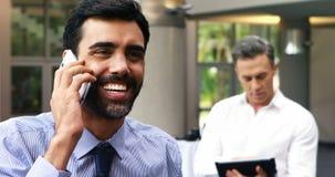 Uitvoerend sprekend op mobiele telefoon zijn collega die digitale tablet gebruiken stock videobeelden