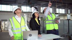 Uitvoerend team die op bouwwerf project bespreken 4 k-luchtkoker van een HVAC-systeem in de bouw Mensencontroles stock video