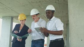 Uitvoerend team die op bouwwerf project bespreken, die smartpone en digitale tablet gebruiken stock video