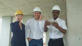 Uitvoerend team die op bouwwerf project bespreken, die tablet gebruiken, die telefoongesprekken hebben met smartphone stock foto