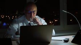 Uitvoerend zakenman drinkwater van glas bij werkplaats in donker bureau stock video