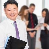 Uitvoerende Aziatische werkgever met zijn commercieel team bij achtergrond Stock Foto