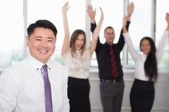 Uitvoerende Aziatische werkgever met zijn succesvol commercieel team bij achtergrond Royalty-vrije Stock Afbeelding